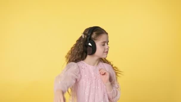 Fiatal lány hosszú hajjal zenét hallgat fekete fülhallgatóval. Közelkép egy rózsaszín ruhás kislányról. 4k, Uhd