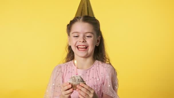 Boldog gyönyörű lány party sapkában elfújja gyertya sárga háttér.