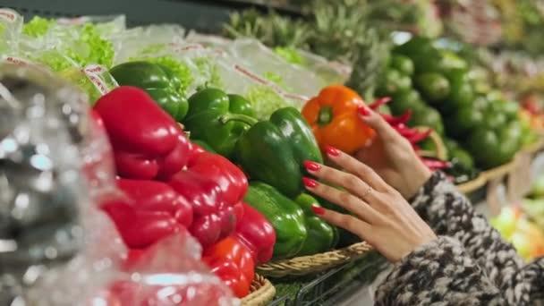 Egy nő, aki piros paprikát vásárol a szupermarketben vagy a zöldségboltban. Közelkép egy nő kezéről, amint épp paprikát vesz ki a friss termékekből. Afrikai amerikai nő a boltban. 4k, Uhd