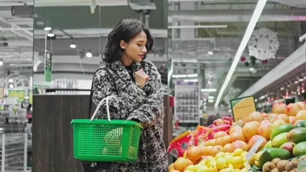 Frau kauft Grapefruits im Supermarkt. Medium einer afrikanisch-amerikanischen Frau, die Grapefruits im Laden auswählt und in den Warenkorb legt. Veganes Verkaufskonzept in 4k, uhd