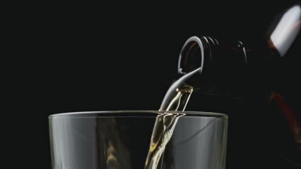Üvegből üvegbe öntött alkohol. Rum folyik a barna üvegből. Közelkép arany whisky öntés fekete háttér.