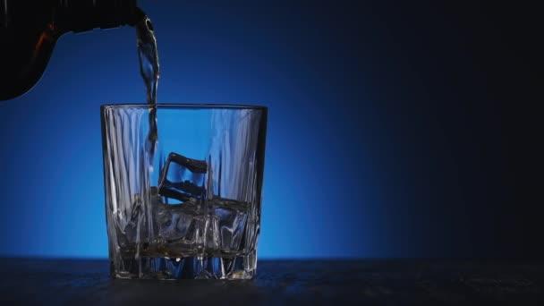 A whiskyt kék hátterű üvegből öntötték üvegbe, jobb oldali másolótérrel. Egy közeli üveg whisky jégkockával. Bourbon whisky öntése lassított felvételben