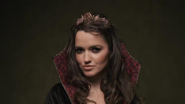 Žena v plášti a koruně. Portrét upírky, jak se dívá do kamery. 4K, UHD
