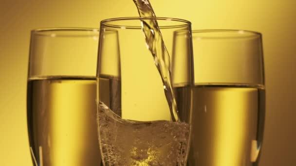 Pezsgőt öntök poharakba. Pezsgő sárga háttérrel
