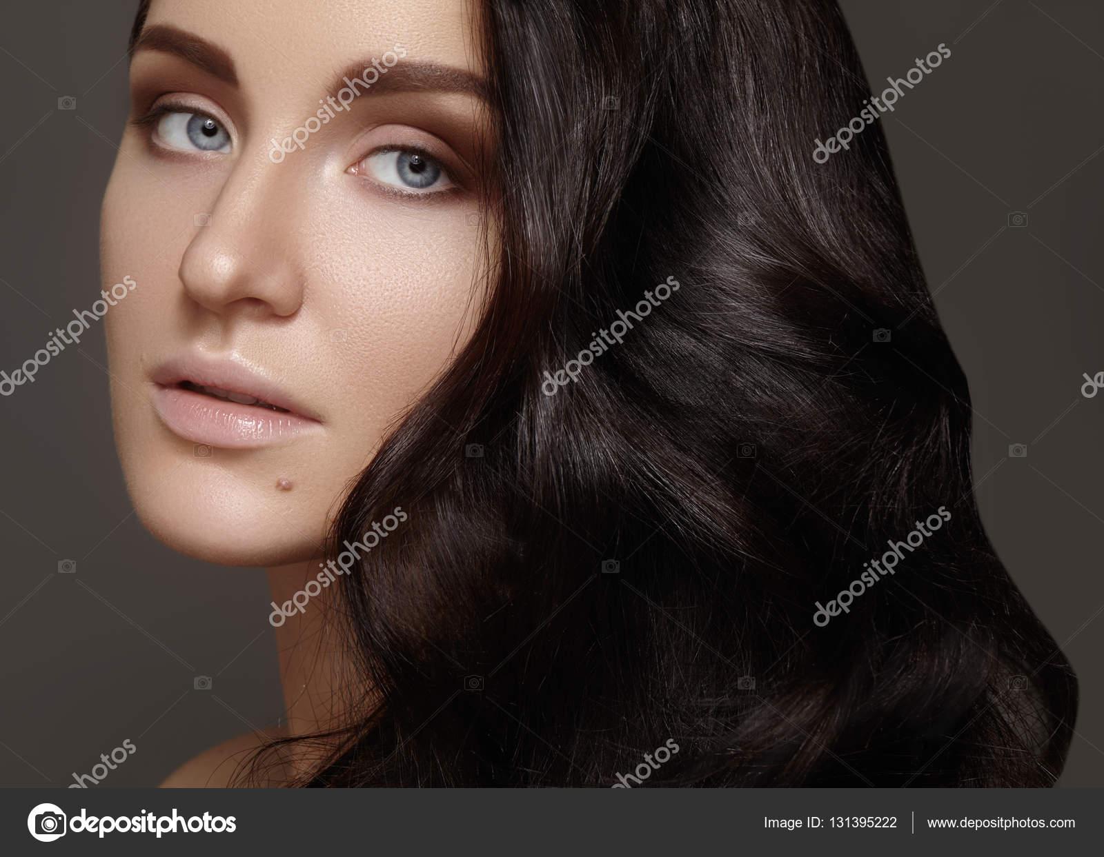 Hermosa mujer joven con peinado rizado volumen. Retrato de belleza de  modelo morena con la piel limpia 1b84ba52c31e
