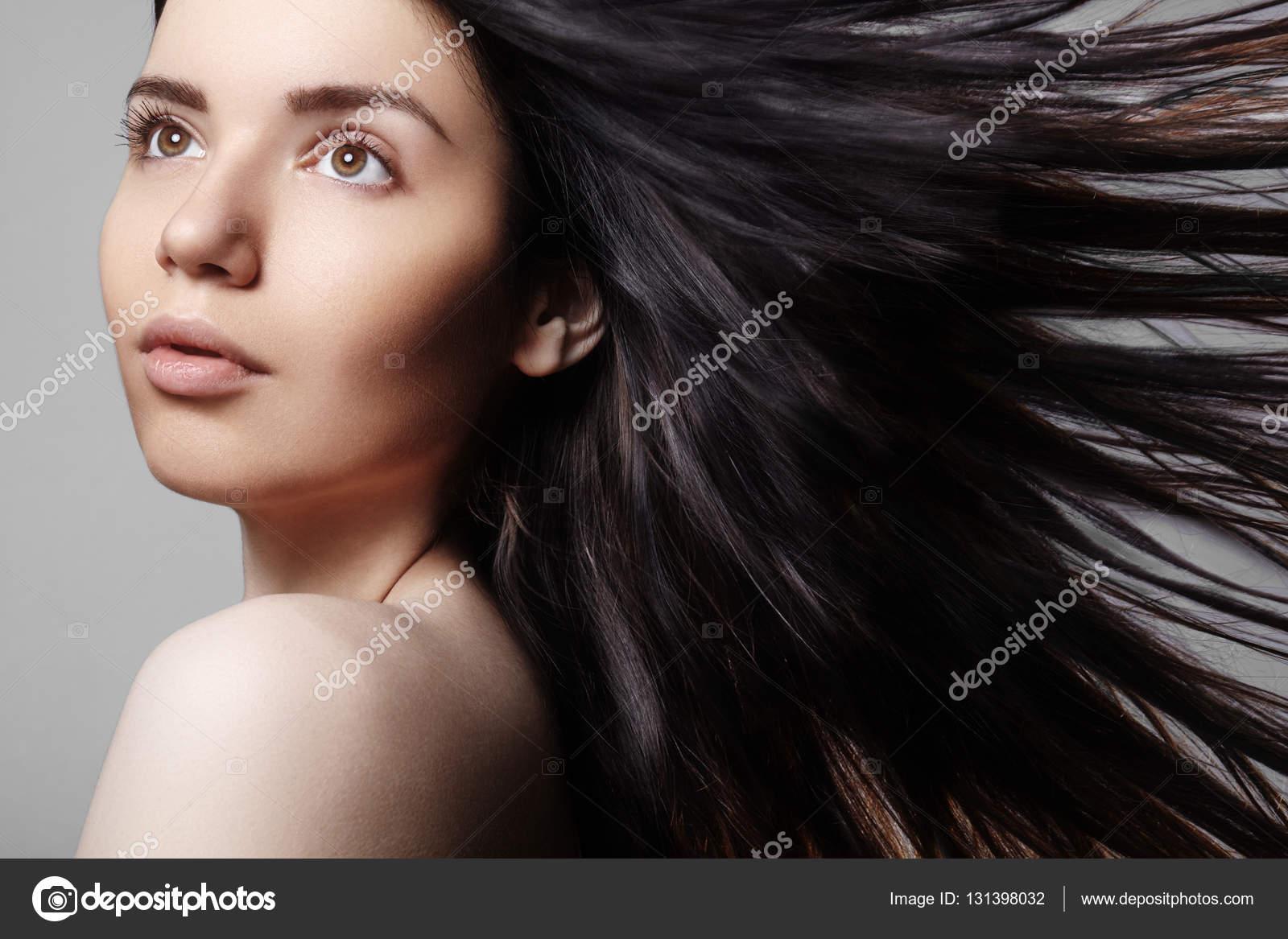 Modello di bella giovane donna con capelli windswept marroni su sfondo  grigio fefb6c45f2b6