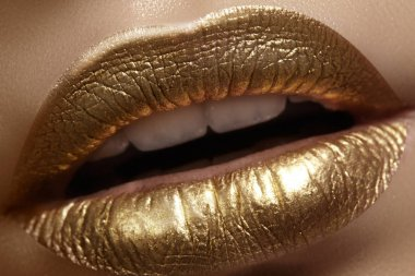 Beautiful closeup with female plump lips with gold color makeup. Fashion celebrate make-up, glitter cosmetic. Christmas style
