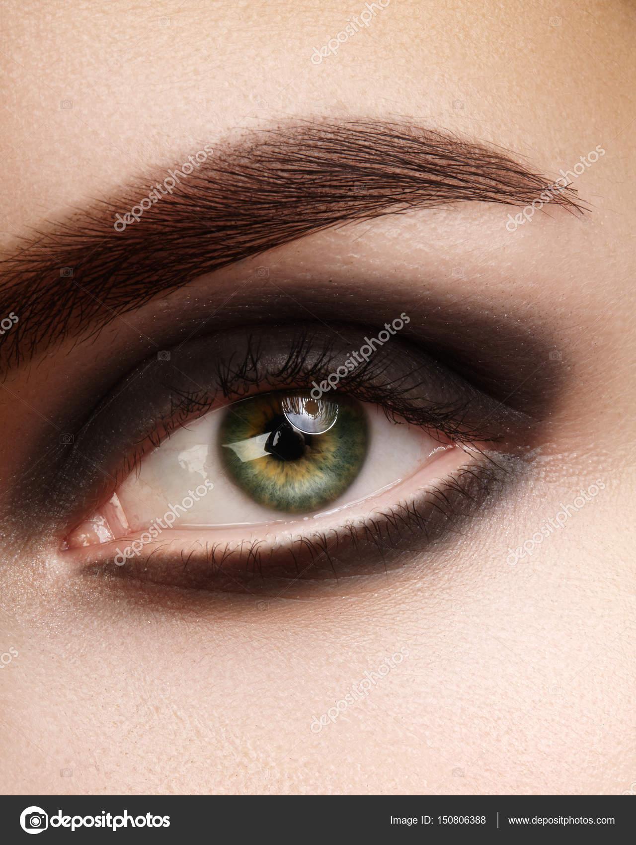 Foto de macro hermoso de ojos de mujer con maquillaje ahumado negro