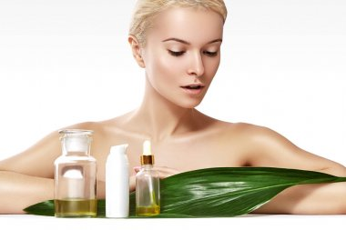 Beautiful woman applies organic cosmetic and oils for beauty. Spa and wellness. Clean skin, shiny hair. Healthcare