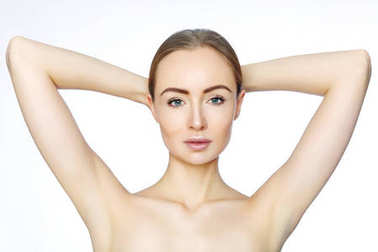 Beautiful woman holding her arms with clean underarms on white background. Epilation smooth skin. Hair removal on arms