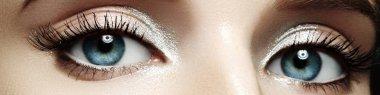 Closeup female eyes with bright make-up, great shapes brows, extreme long eyelashes. Celebrate makeup, luxury eyeshadows