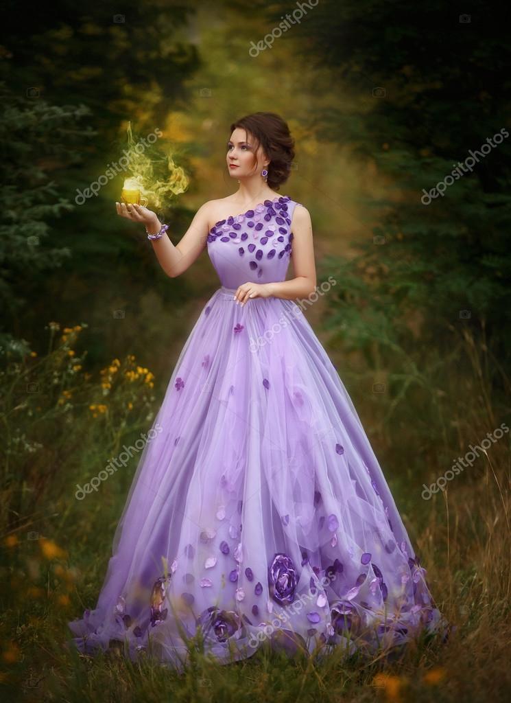 Hermosa chica en un magnífico vestido largo morado, sosteniendo una ...