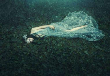 Sleeping Beauty. The girl lies on the grass