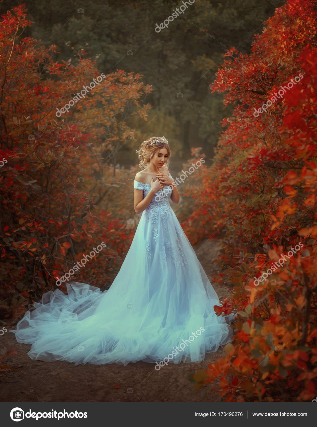 Молодая принцесса гуляет в красивом голубом платье ...