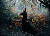 Beauty Gothic princess walks in autumn forest. Fantasy mystical dark backdrop.