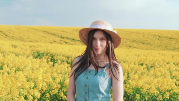 Young beautiful happy charming woman standing in flowering field. Yellow natural flowers rape. Cute smiling face. Brunette girl long hair. Creative pink summer hat, denim sundress. Backdrop blue sky