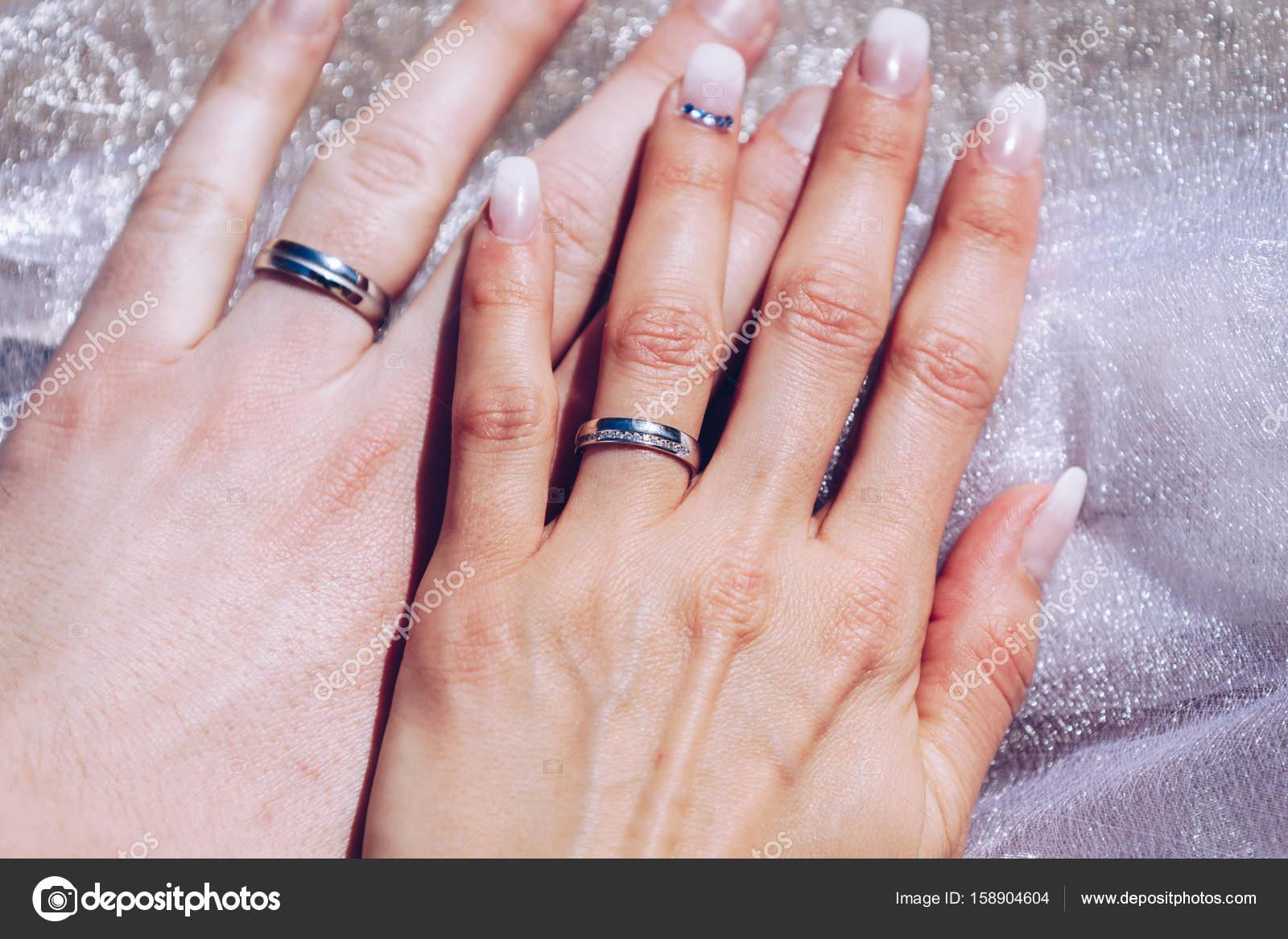 Recién casados las manos de la pareja con los anillos de boda ...