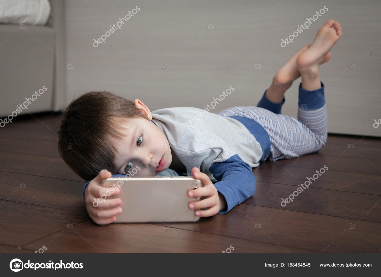 Niño Acostado Piso Mira Algo Interesante Gadget