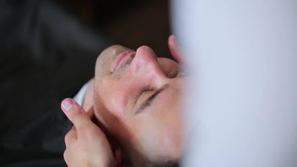 auf das Gesicht des Mannes wird Aftershave aufgetragen
