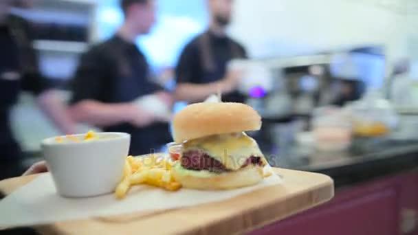 Dívka číšník přináší burger