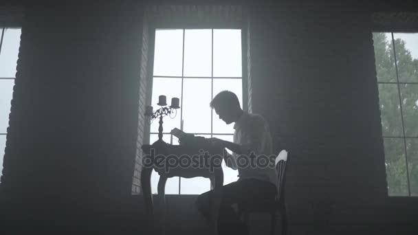 hombre escribiendo en una máquina de escribir en un cuarto oscuro ...
