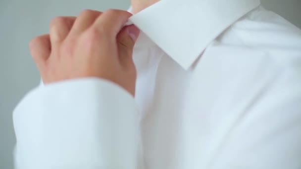Uomo abbottonarsi una camicia bianca