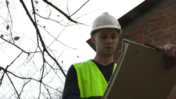 Builder in a helmet looking at drawings