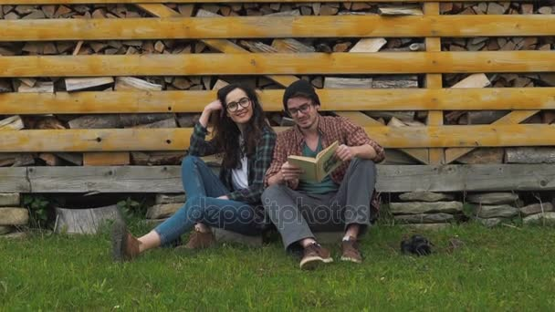 Couple reading book on the background of firewood