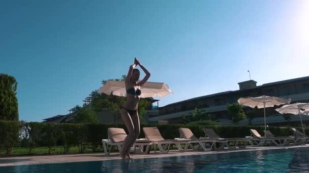 Dívka skákající do bazénu