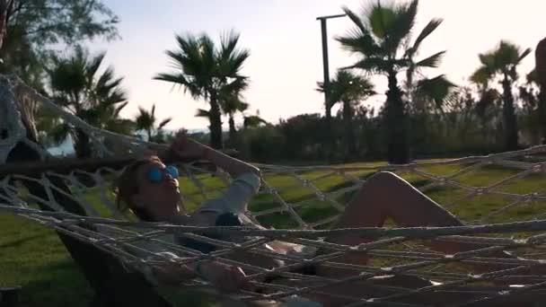 a lány a fürdőruhát fekszik egy függőágyban közelében palms