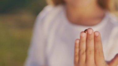 A lány ujjai katicabogár