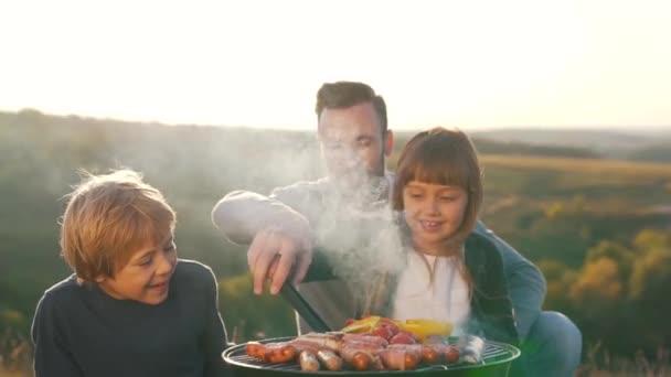 Otec s dětmi vařit párky na grilu