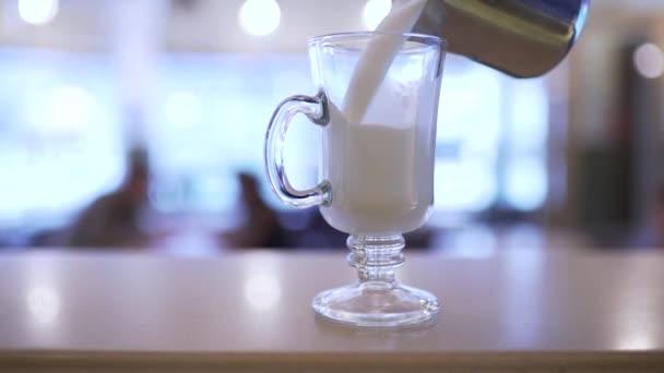 barman nalévá mléko do sklenice