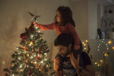 Girl and dad setting up the christmas tree with star, lights and