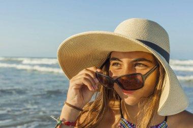 Girl at the beach wearing beach summer hat and sunglasses admiri