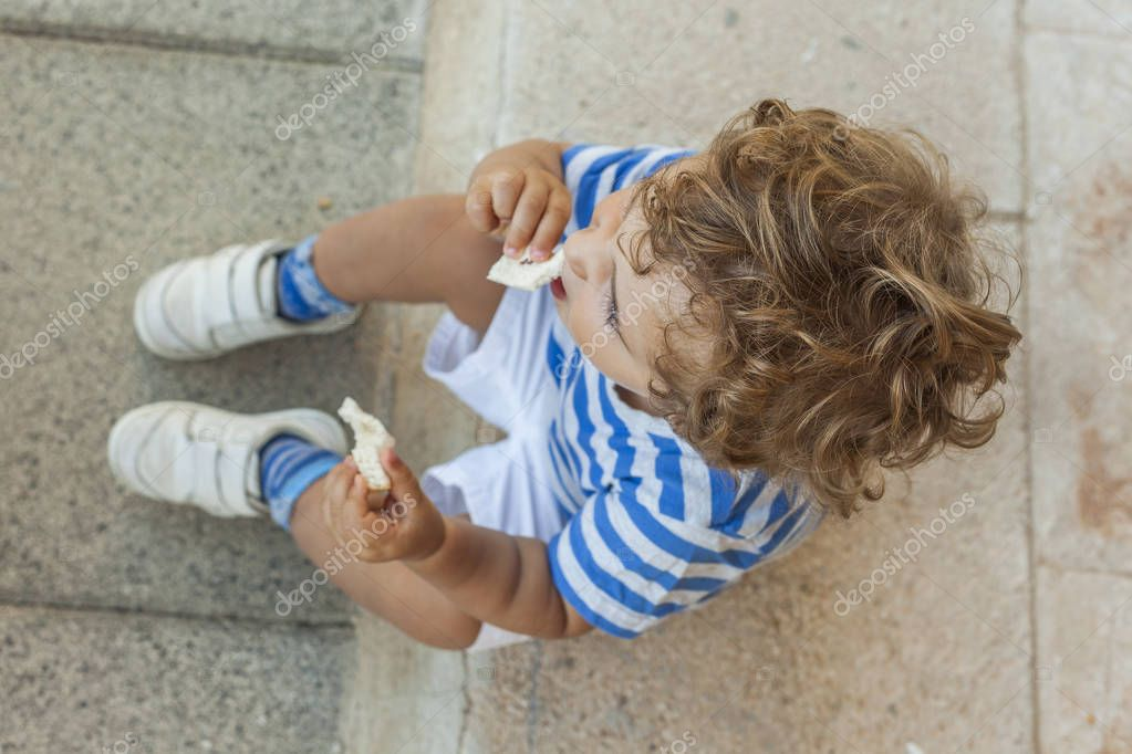 High angle baby boy having a snack in the playground in summertime