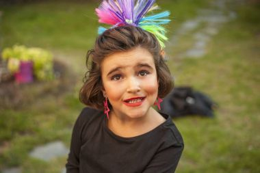 Portrait child dressed as a rocker with star earings and rainbow