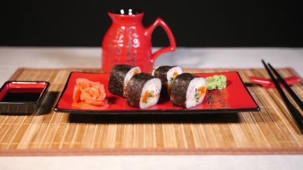 Japanese sushi on red plate with chopsticks on bamboo Background