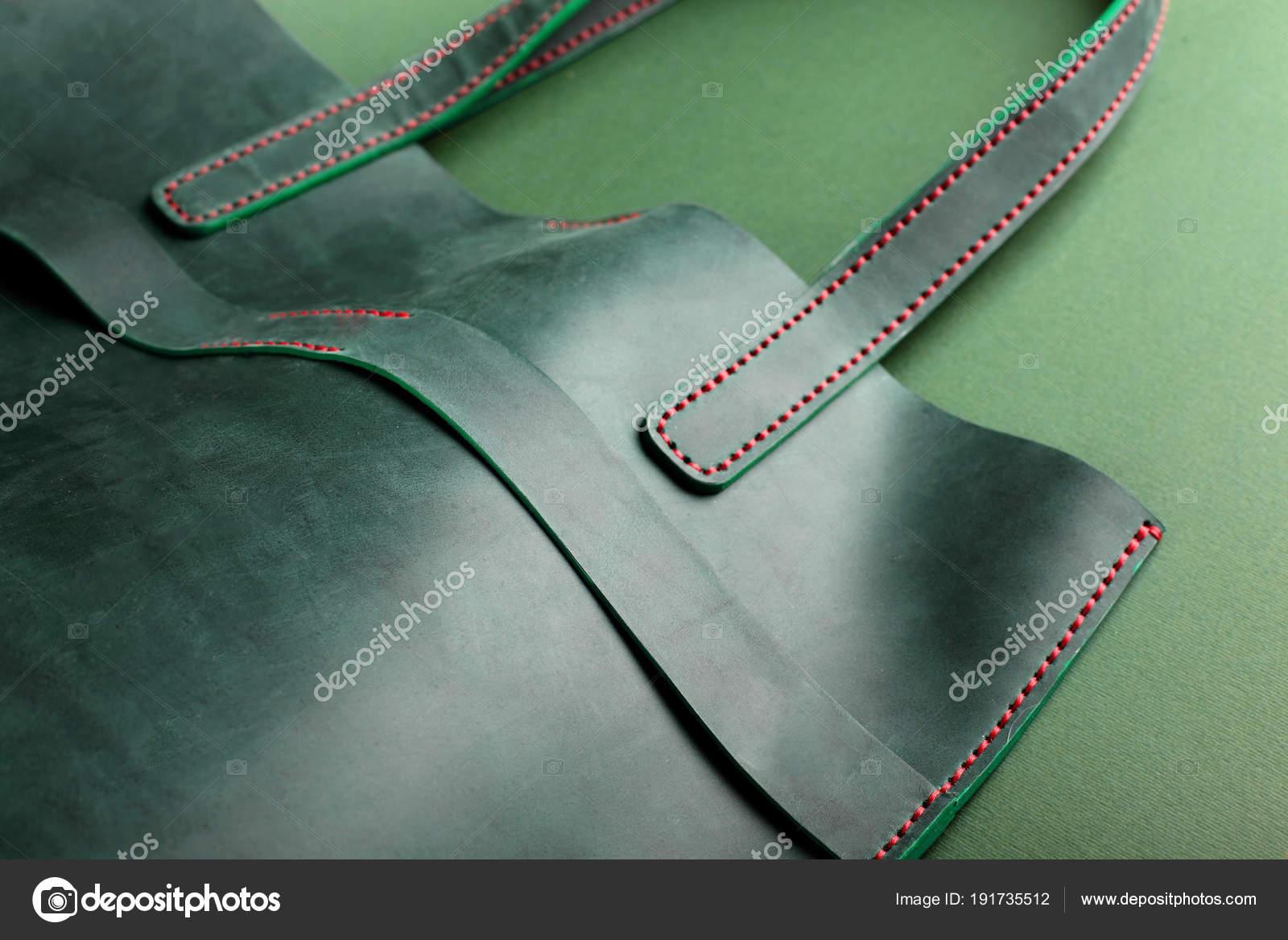 Ženy kožená zelená kabelka na zeleném pozadí. Detailní kopie prostor.  Kožené ručně dělané výrobky eeb97be943