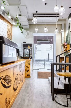 Stylish. Modern interior of cafe.Authentic style with element of loft.Metal and wooden detail.Coffee machine. Green, orange,white and grey colors
