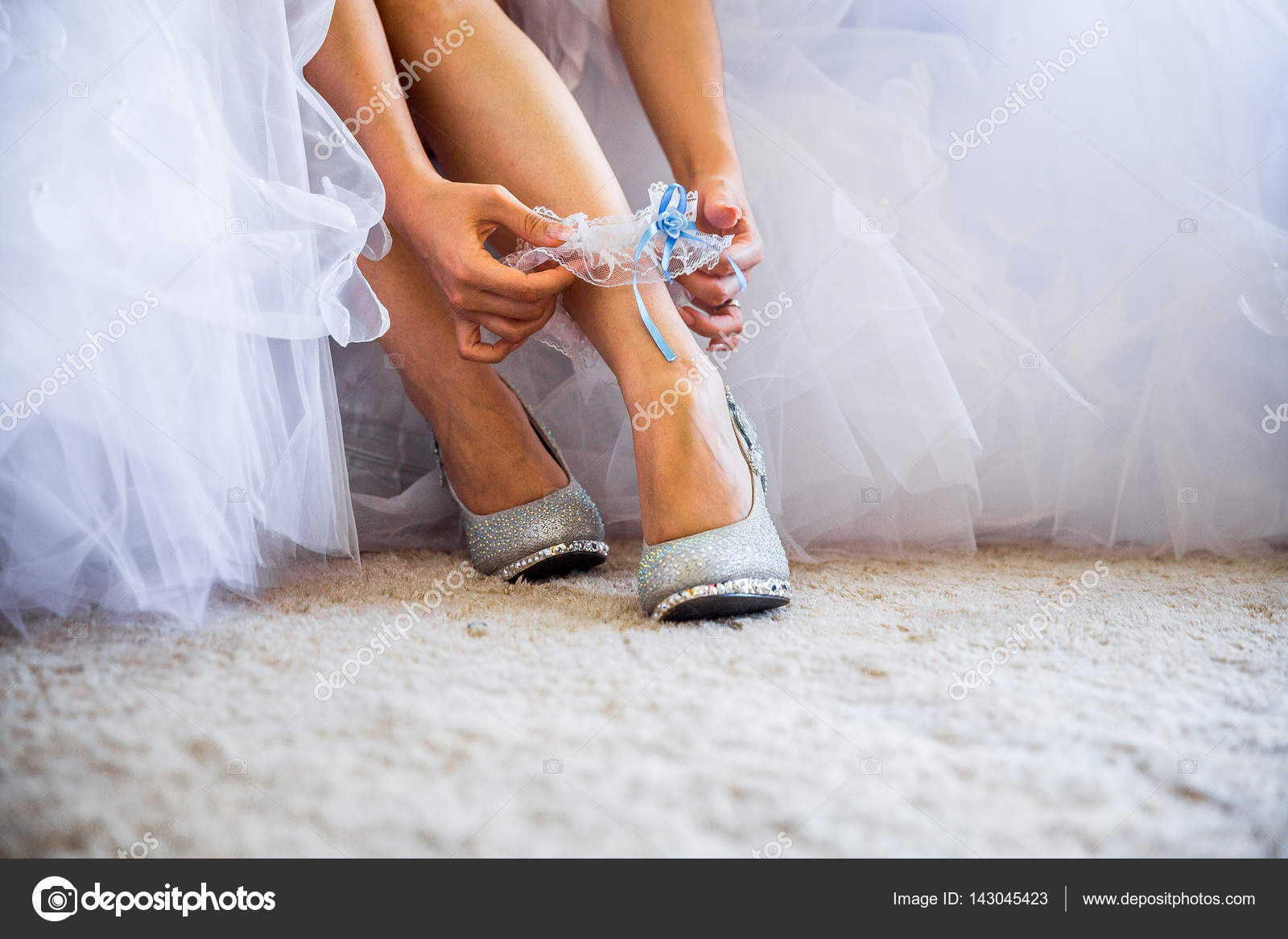 Beautiful shiny shoes standing in front of a bouquet. Callers silver shoes.  Wedding shoes bride stilettos adorned with precious stones. Bride in