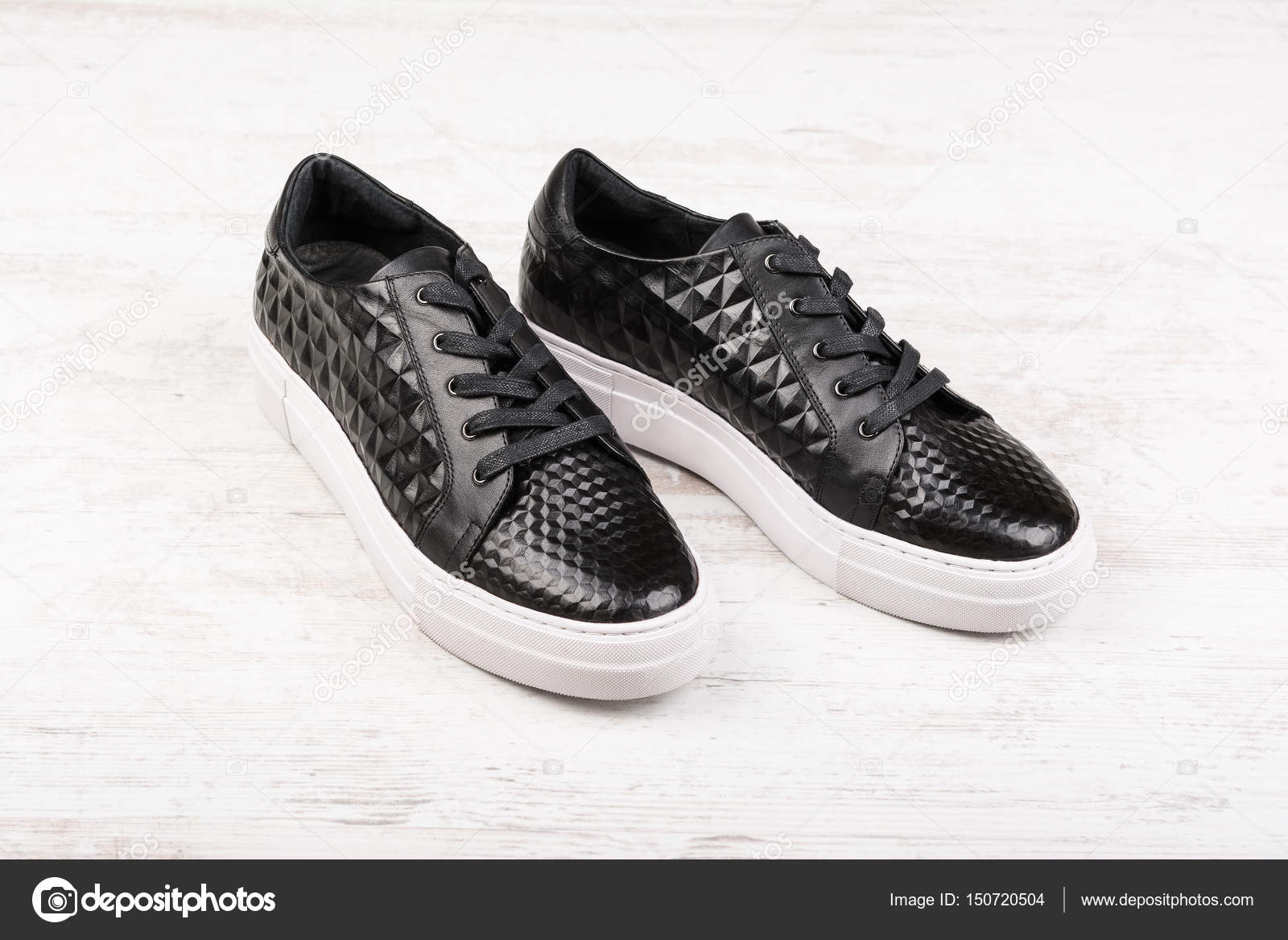 eec4e26cd63 Ζευγάρι μαύρα γυναικείο δερμάτινα αθλητικά παπούτσια σε άσπρο φόντο ξύλινη  — Εικόνα από ...