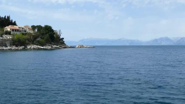 Das Dorf Kassiopi, Korfu, Griechenland. Felsige Küste des Ionischen Meeres und Häuser auf dem Hügel.