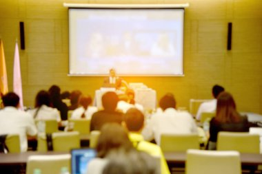 Blurred image of education people, business people and students sitting in large hal with screen and projector for showing information