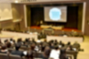 Education concept. Abstract blurred background image of education people, business people and students sitting in conference room or large hall with screen and projector for showing information.