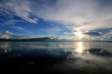 Beautiful sunset and evening sky with mountain and clouds and sunset reflected in the lake for background. Countryside Landscape Under Scenic Colorful Sky At Sunset Dawn Sunrise.