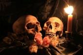 Fotografie Liebhaber menschlicher Totenköpfe und Rosenblüten mit Lichterkerze in schummrigen Valentinstagen auf schwarzem Stoff mit Textur in der Nacht / Stillleben
