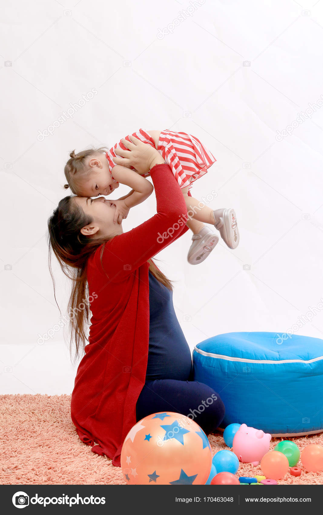 e84690808 Happy young pregnant mother with red knitting sweater playing with ...