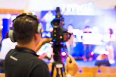 blurred image of young cameraman using a professional camcorder in door at event filming music show or mini concert for shooting some video movie and live broadcasting for online TV commercial