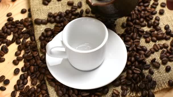 Nalít kávu z Turka do bílého šálku. Burlap a dřevo pozadí.